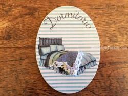 Placa de dormitorio con cama y fondo turquesa (con texto DORMITORIO)