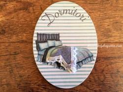 Placa de dormitorio con cama y fondo turquesa (con texto DORMITORI)